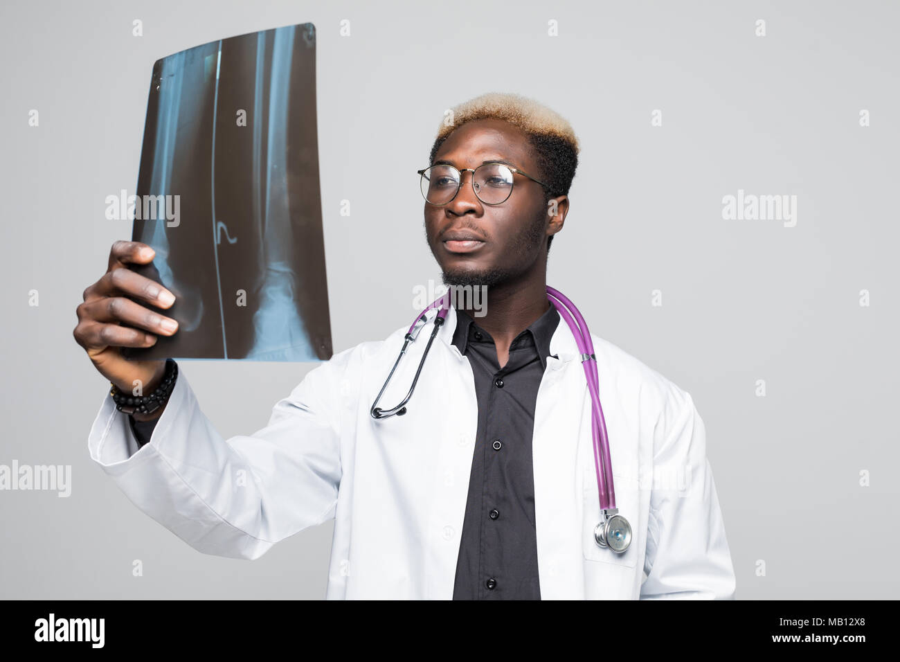 Portrait of a doctor looking at a radiography - Stock Image