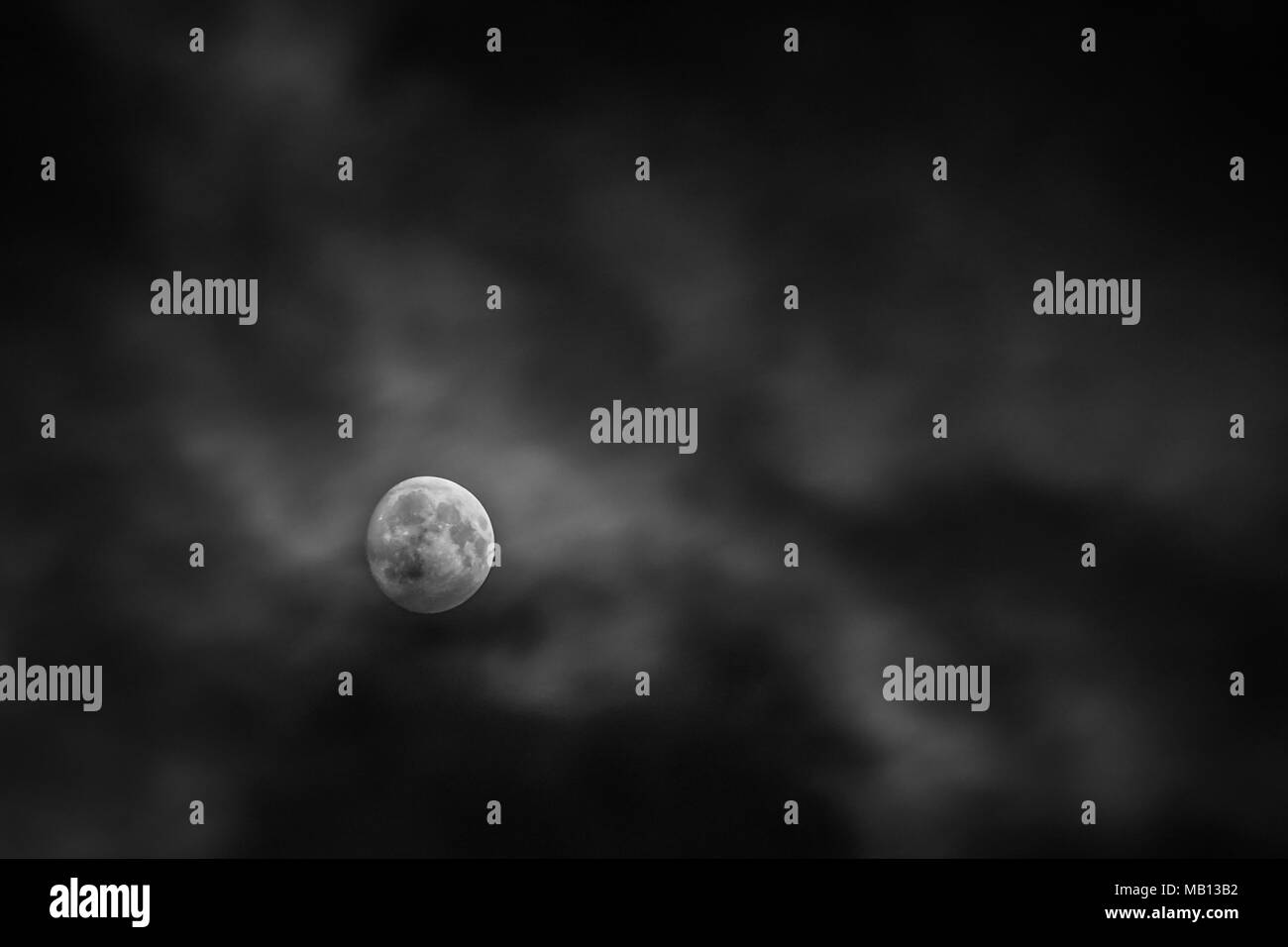 Full moon behind blur clound at midnight - Stock Image