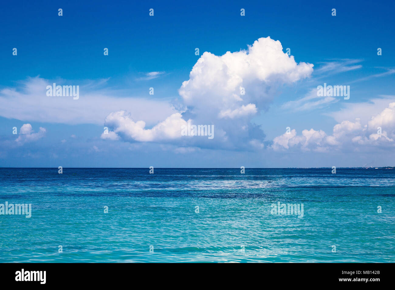 the Caribbean. A saturated blue sky, clouds and the sea. - Stock Image