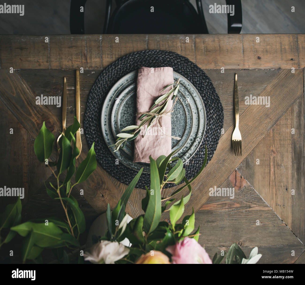 Flat-lay of Spring Easter holiday Table setting. Tender blossom flowers, plates and cutlery over vintage wooden table, top view - Stock Image