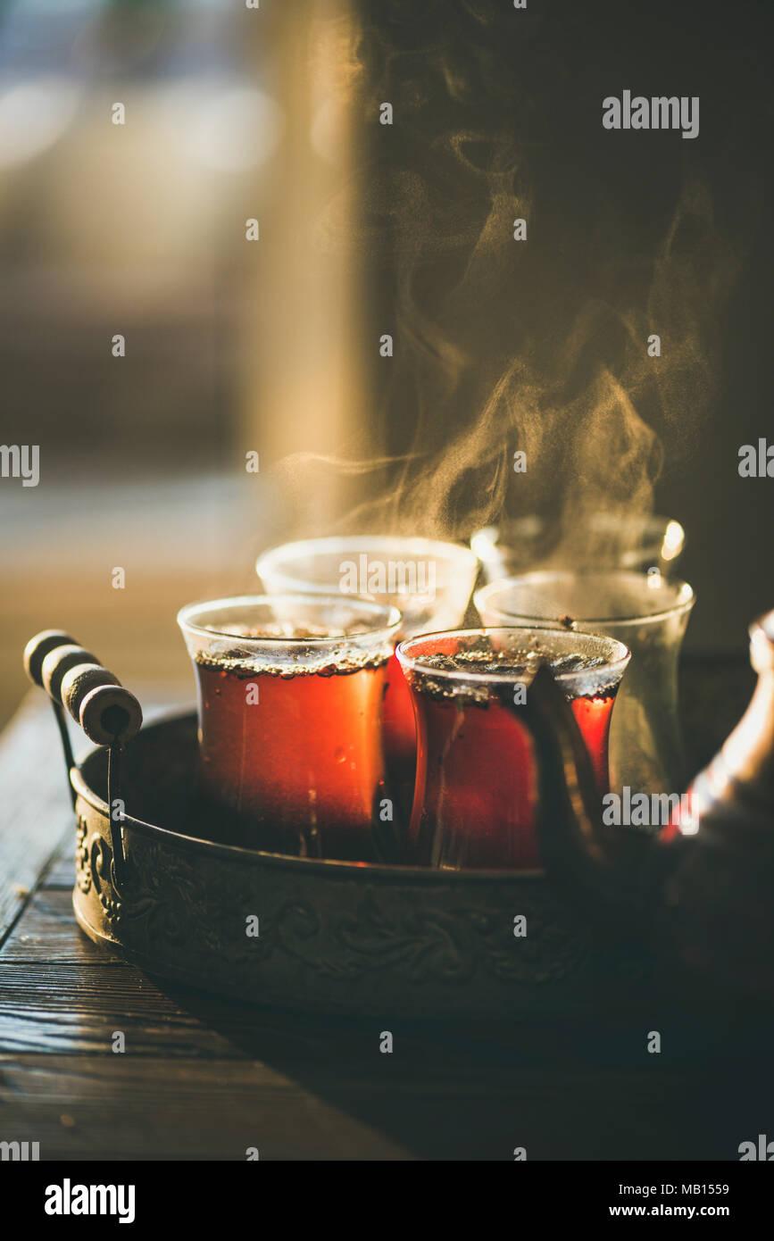 Freshly brewed black tea in turkish glasses in oriental tray, selective focus, copy space - Stock Image