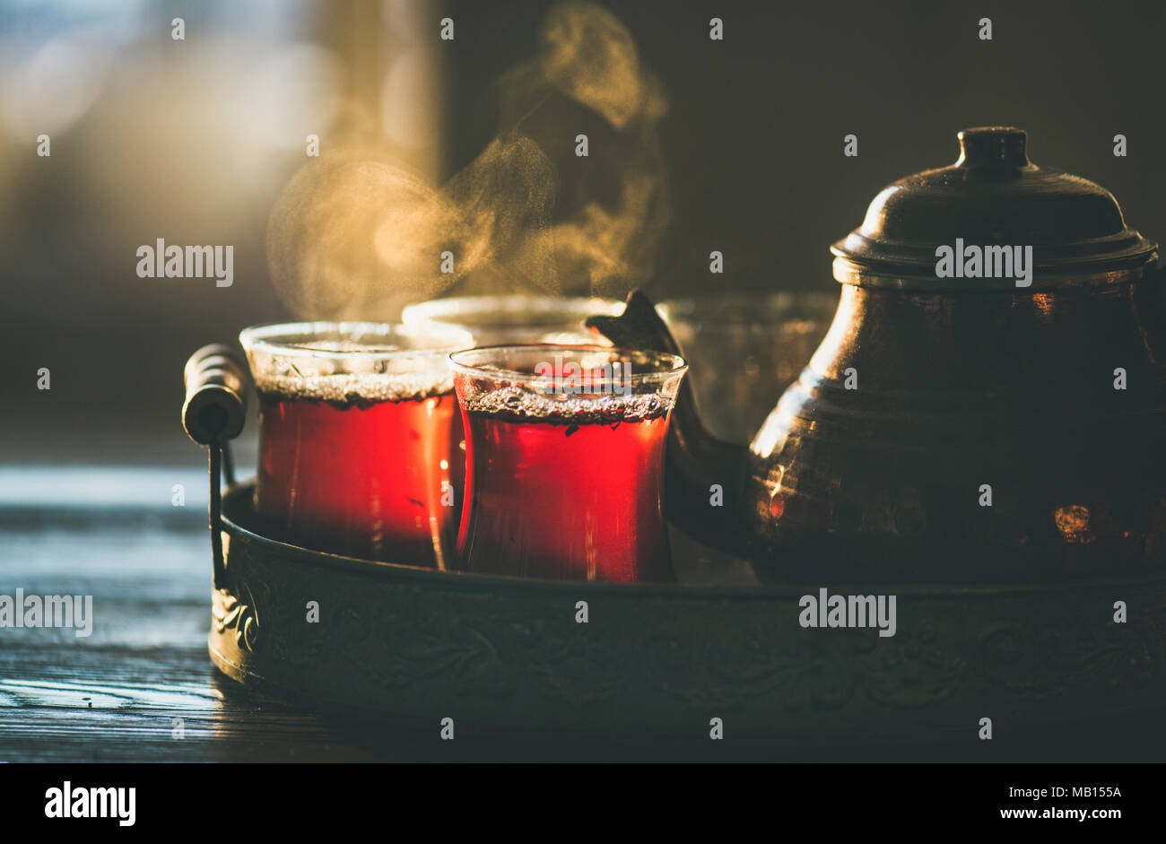 Freshly brewed black tea in turkish glasses and teapot in oriental tray, selective focus - Stock Image
