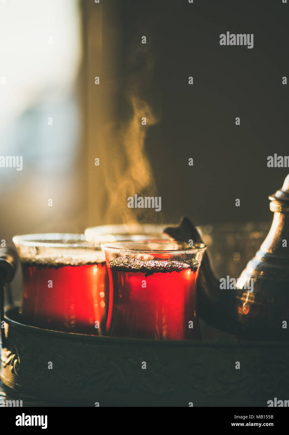 Freshly brewed black tea in turkish glasses and teapot in oriental tray, selective focus, close-up, copy space - Stock Image