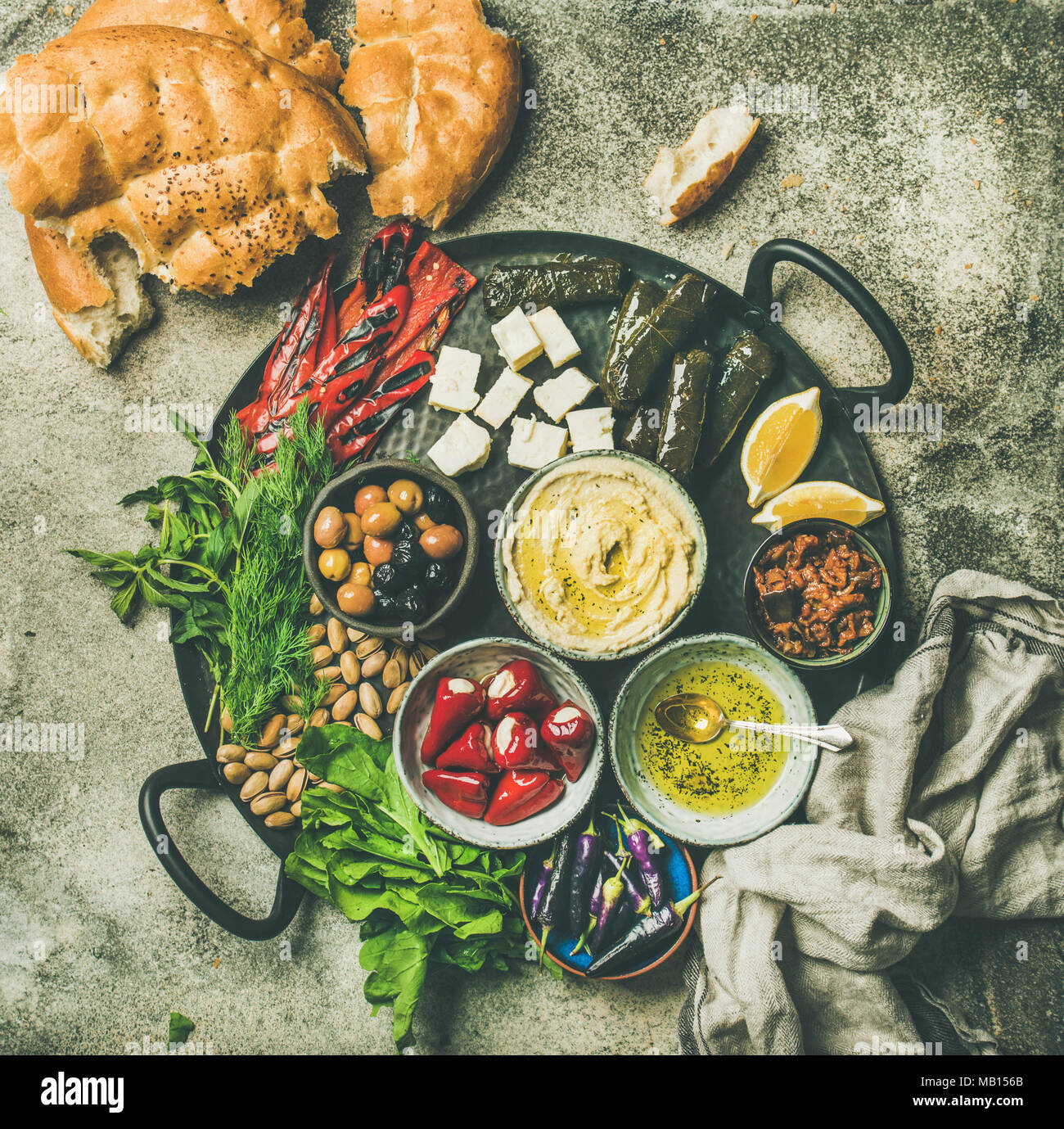 Mediterranean, Middle Eastern meze starters platter. Flat-lay of stuffed pickled paprikas, cheese, dolma, hummus, spiced oil, olives, sundried tomatoe - Stock Image