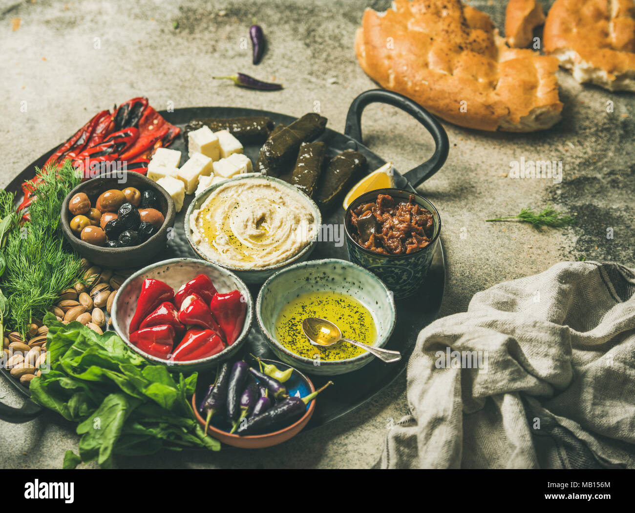 Mediterranean, Middle Eastern meze starter platter. Stuffed pickled paprikas, dolma, hummus, spiced oil, olives, sundried tomatoes, nuts, cheese, flat - Stock Image