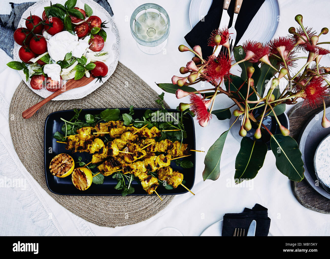 Table setting of mediterranean salad and grilled turmeric chicken skewers. - Stock Image