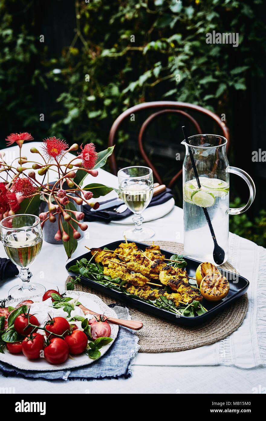 summer picnic: mediterranean salad, turmeric chicken skewers. - Stock Image