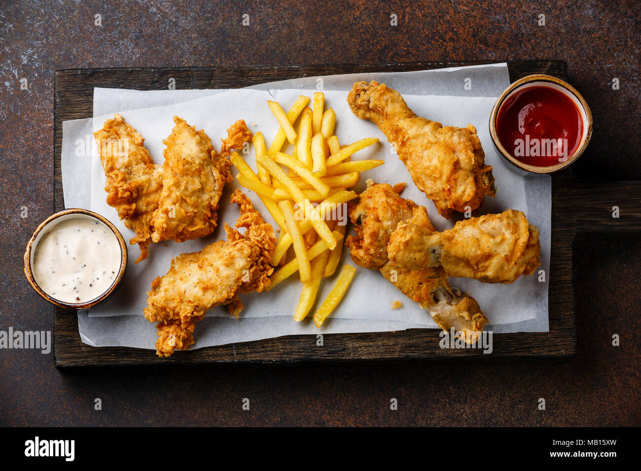Fried breaded chicken legs fast food with popular sauce on brown background - Stock Image