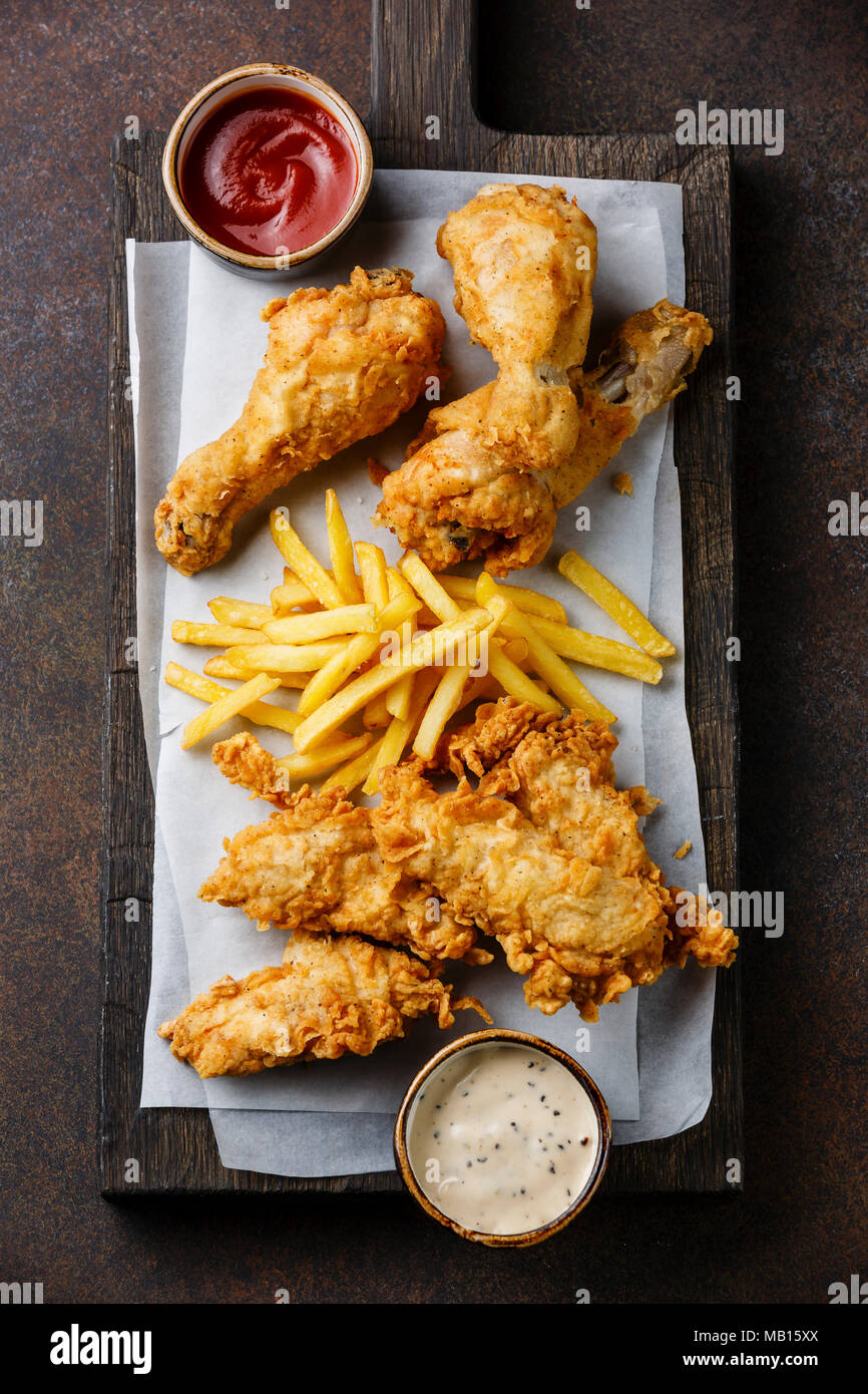 Fried breaded chicken legs fast food with popular sauce on brown background Stock Photo