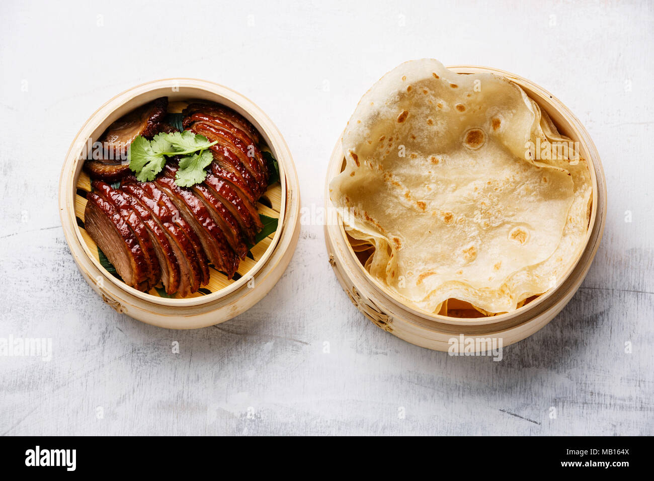 Sliced Peking Duck in bamboo steamer served with fresh roasted wheaten chinese pancakes on white background - Stock Image