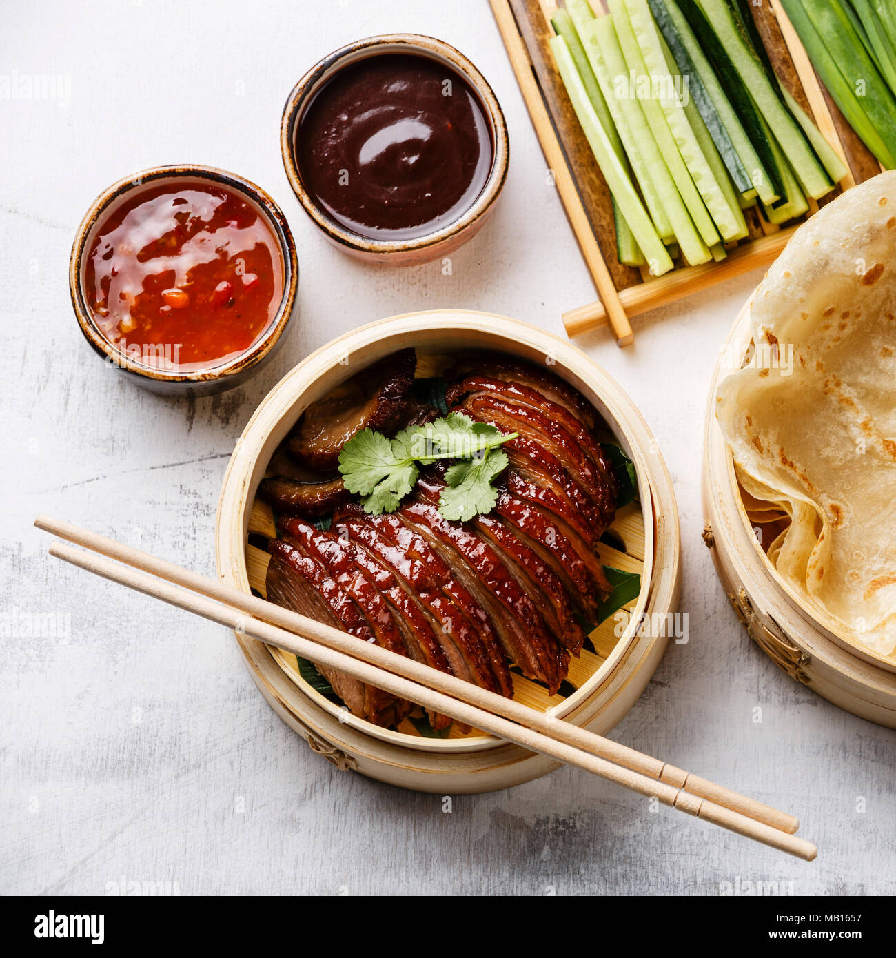 Sliced Peking Duck in bamboo steamer served with fresh cucumber, green onions, cilantro and roasted wheaten chinese pancakes with sauce Hoysin on whit - Stock Image
