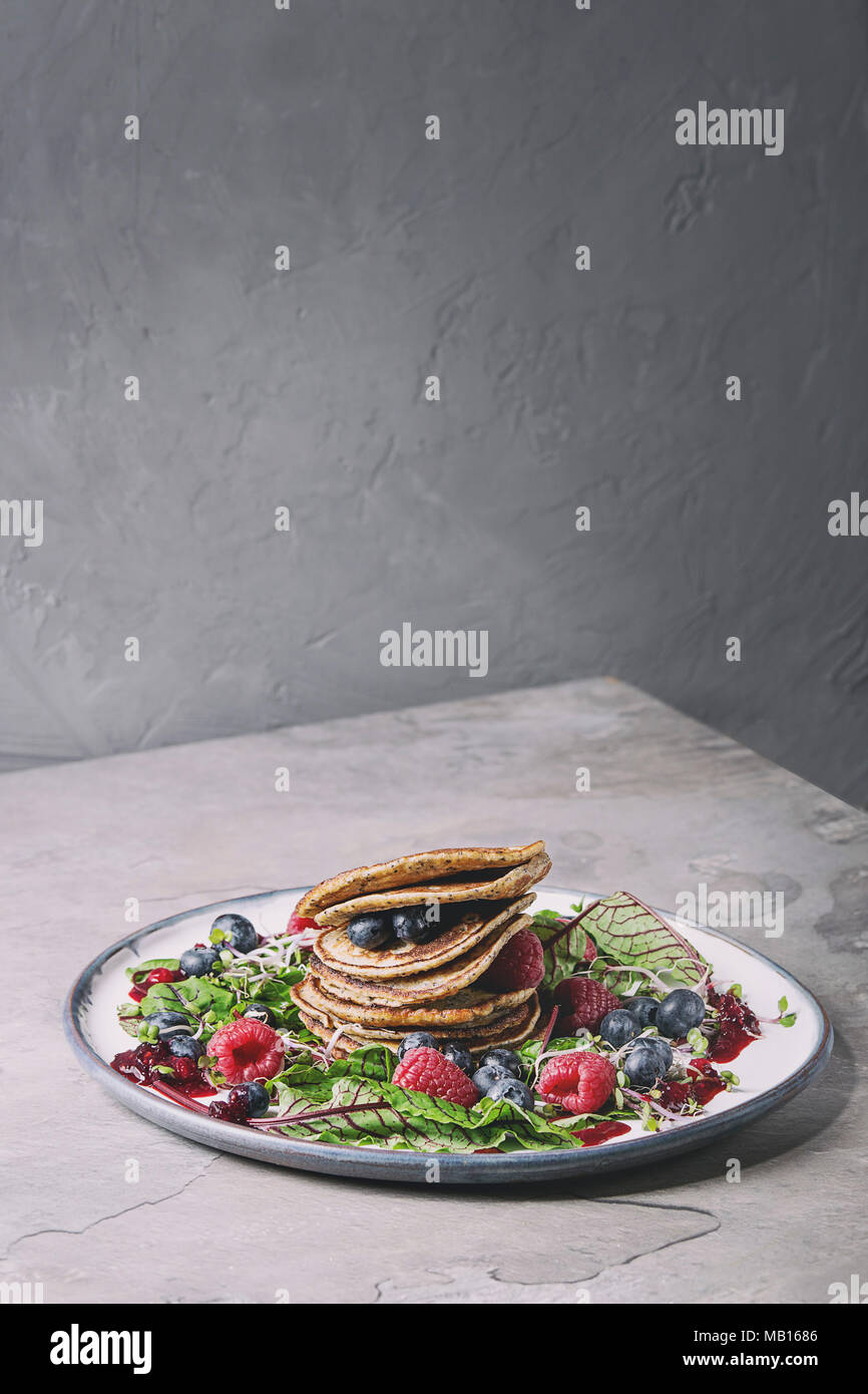Vegan chickpea pancakes served in plate with green salad young beetroot leaves, sprouts, berries, berry sauce over grey kitchen table. Copy space. Hea - Stock Image
