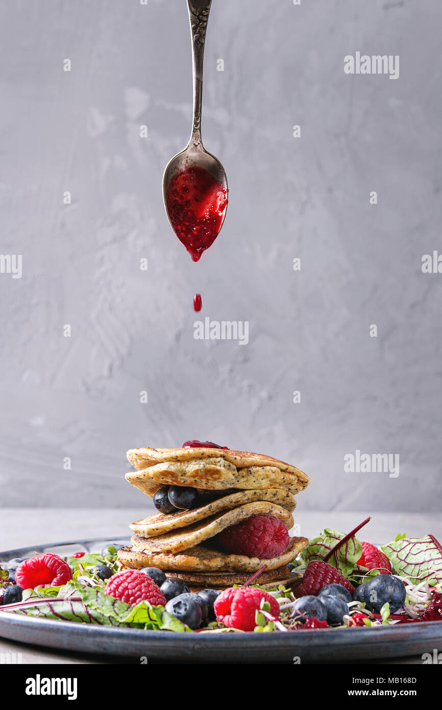 Vegan chickpea pancakes served in plate with green salad young beetroot leaves, sprouts, berries, berry sauce flowing from spoon over grey kitchen tab - Stock Image