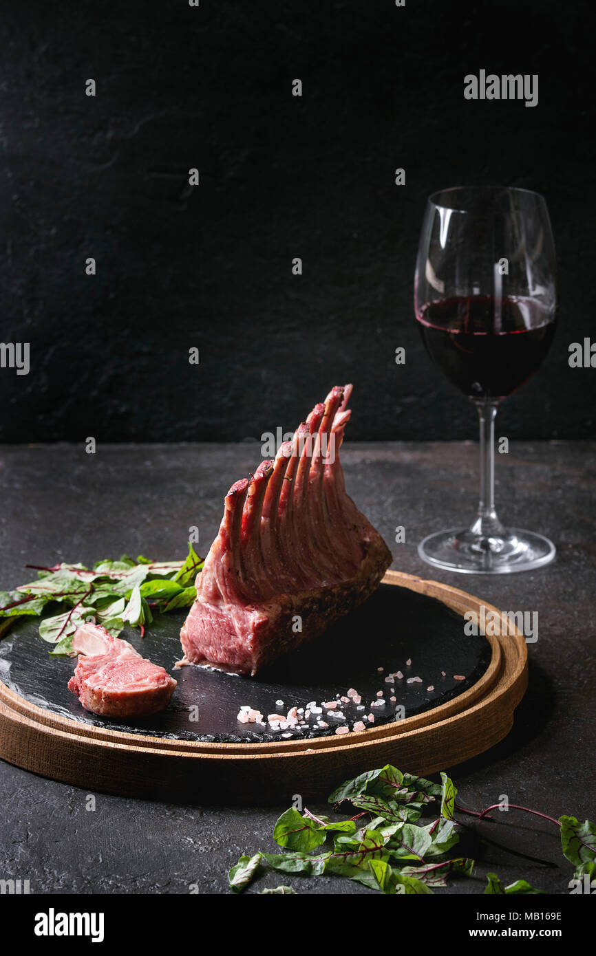 Grilled sliced rack of lamb with yogurt mint sauce served with green salad young beetroot leaves, glass of red wine, pink salt on round wooden slate b Stock Photo