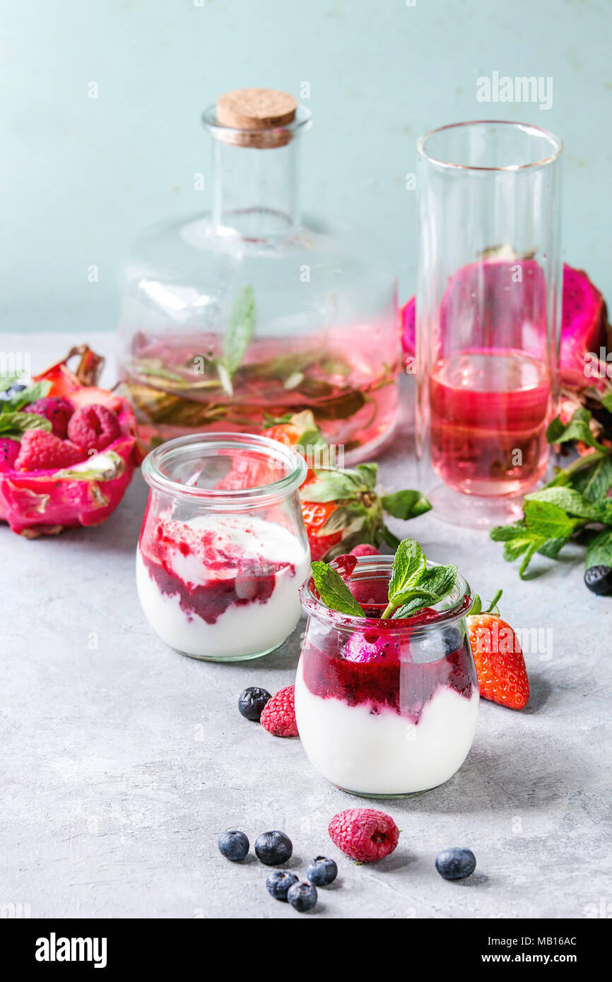 Jars of natural white yogurt with berry sauce, fruit salad with pink dragon fruit, berries and mint, served with bottle of lemonade on grey table. Hea - Stock Image