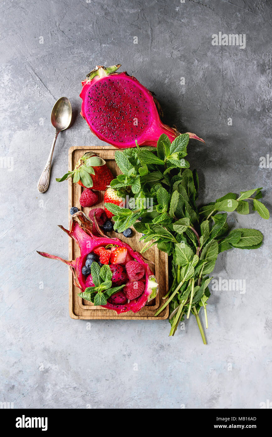 Vegan fruit salad with berries and mint served in pink dragon fruit with ingredients above on wooden serving board over blue texture background. Top v Stock Photo