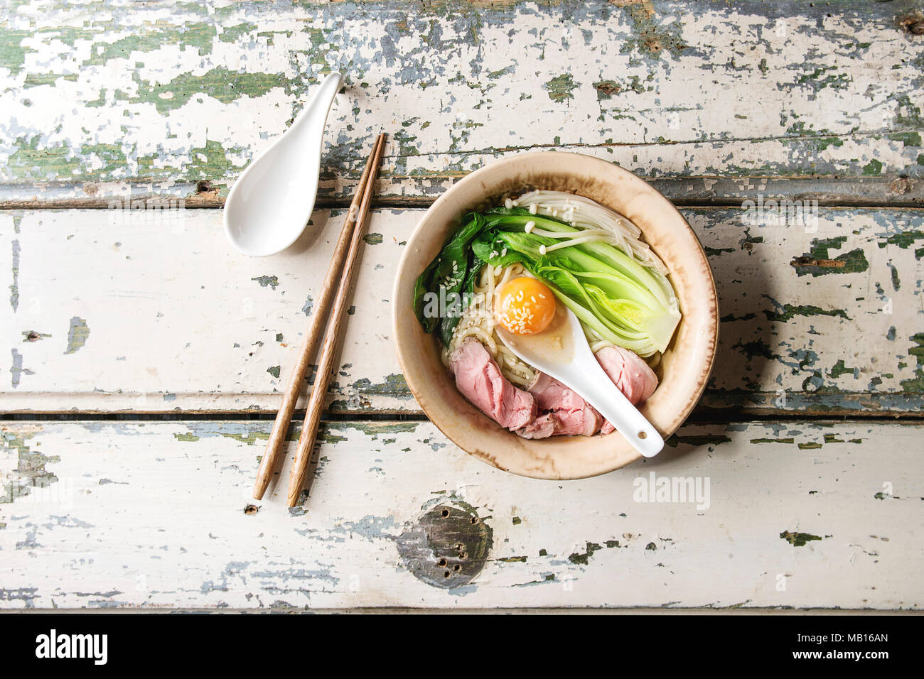 Asian dish udon noodles with egg yolk, sesame, mushrooms, boc choy, sliced sous vide cooked meat served in ceramic bowl with spoon and chopsticks over Stock Photo
