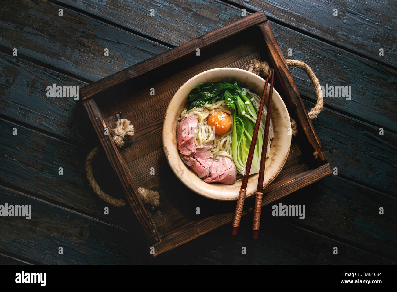 Asian dish udon noodles with egg yolk, sesame, mushrooms, boc choy, sliced sous vide cooked meat served in ceramic bowl with spoon and chopsticks on w - Stock Image