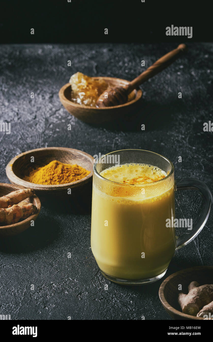Cup of ayurvedic drink golden milk turmeric latte with curcuma powder and ingredients above over black texture background. Toned image - Stock Image