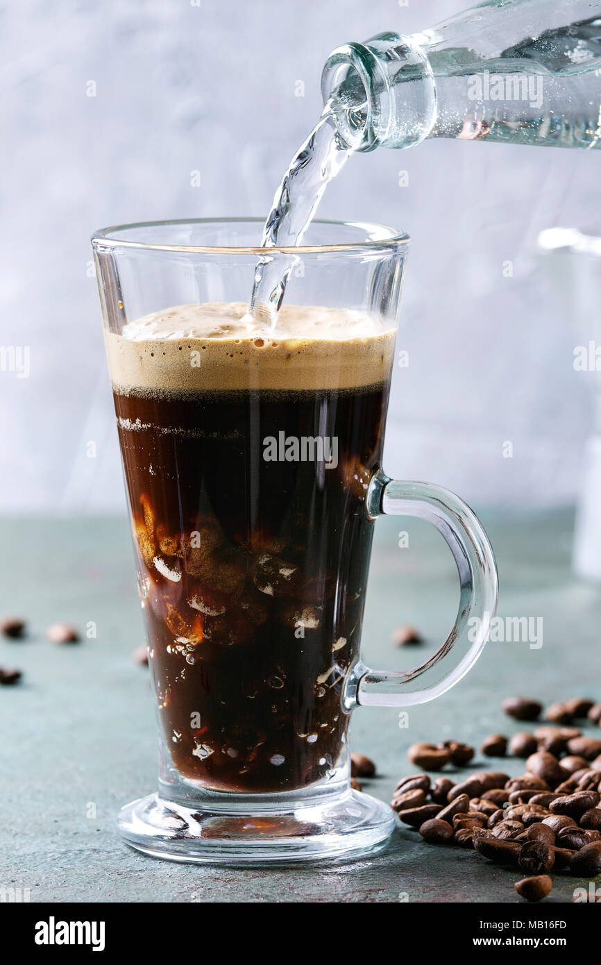 Fizzy iced Coffee espresso with pouring sparkling water from bottle and roasted beans around over grey green texture table. Modern drink. - Stock Image