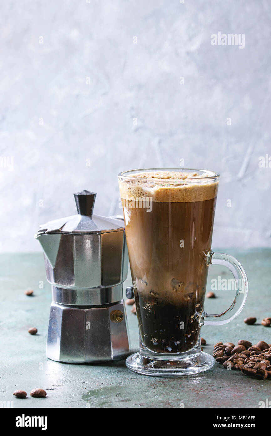 Fizzy iced Coffee espresso with milk, coffee maker and roasted beans around over grey green texture table. Modern drink. Copy space - Stock Image