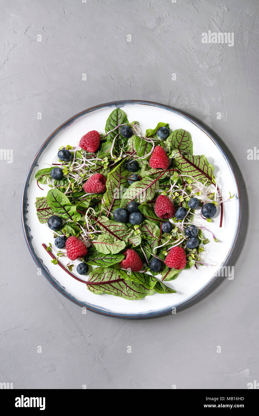 Green vegan salad with berries strawberry, blueberry, sprouts, young beetroot leaves on ceramic plate over grey concrete background. Top view, space.  - Stock Image