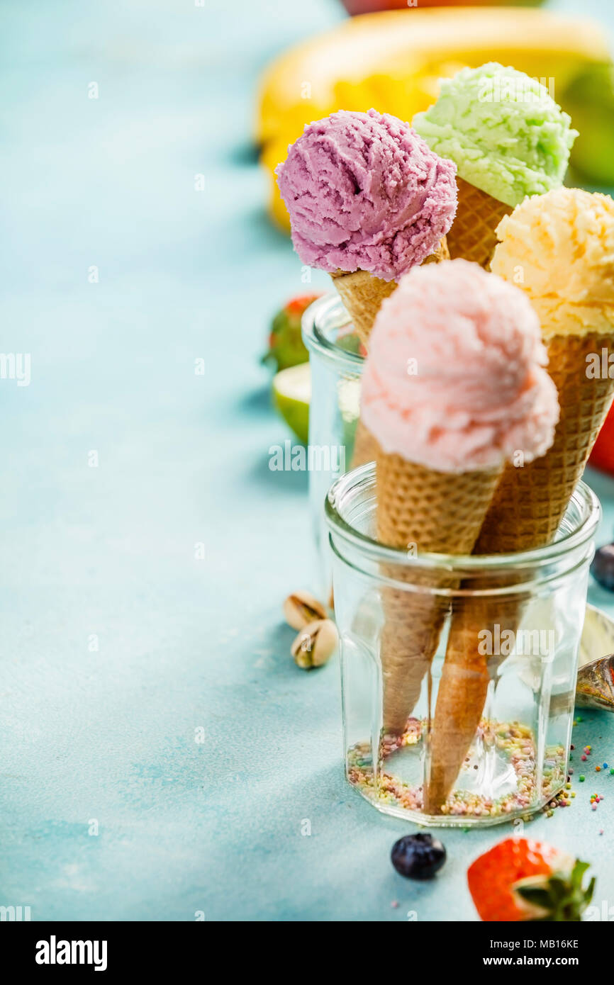 Various of ice cream flavor in cones pink (strawberry, raspberry), purple (blueberry), green (pistachio, green tea, lime) and yellow (mango, banana) s - Stock Image