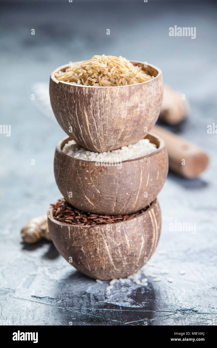 Assortment of different rice in bowls: Rice berry, Brown rice and Risotto rice on grey stone background. - Stock Image