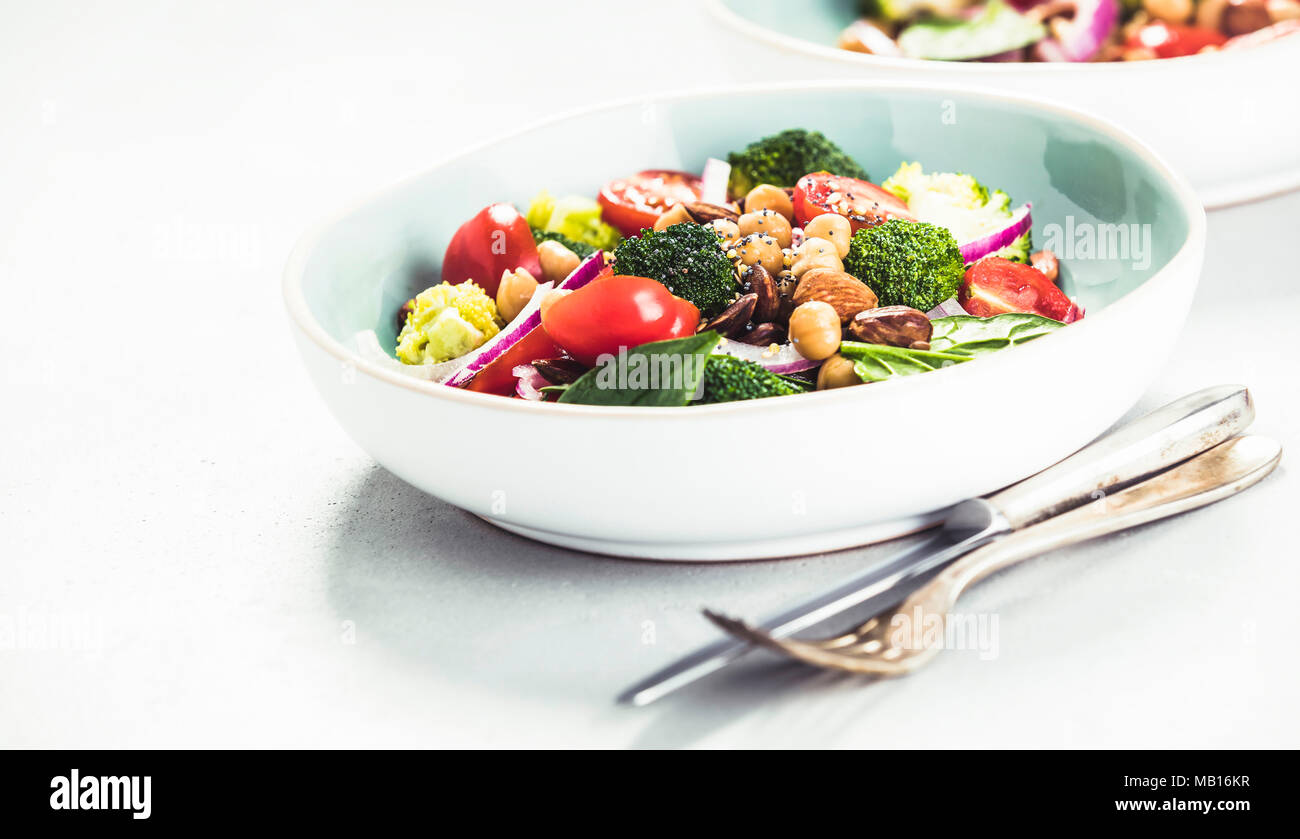 Healthy vegan energy boosting salad with chickpeas, broccoli, tomatoes, red onion, spinach and nuts in blue plate on concrete background, selective fo - Stock Image