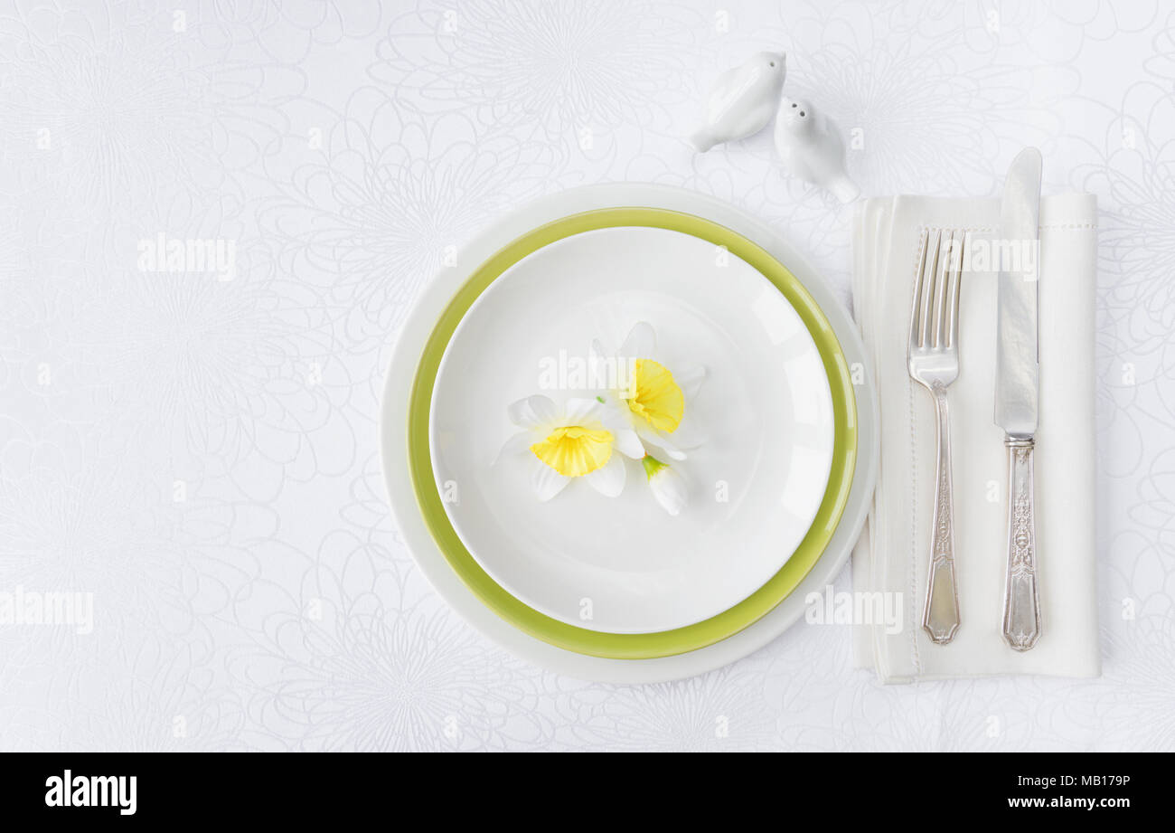 Classic serving for a gala dinner with luxurious porcelain, silverware and spring flowers on a white tablecloth, with copy-space Stock Photo
