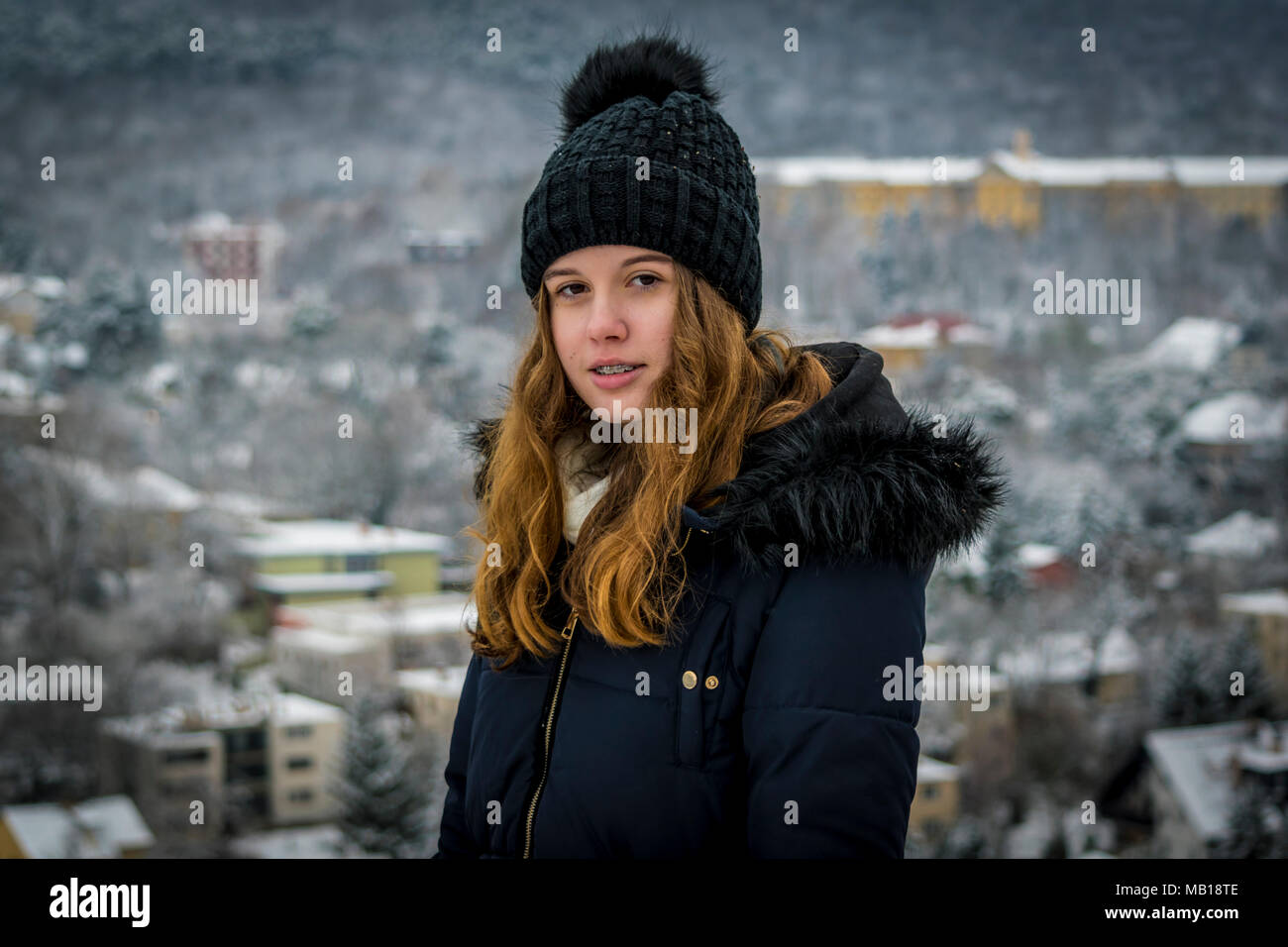 Half body portrait of beautiful Caucasian teenage girl at winter. Pretty teen girl in snow, facing camera, blurred snowy city in background. - Stock Image