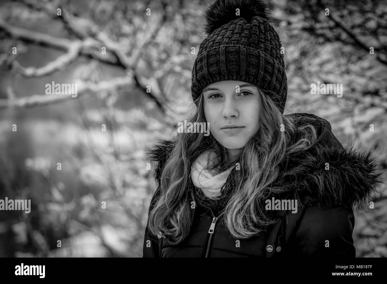 Closeup portrait of pretty teen girl at winter black and white beautiful caucasian teenage girl in black coat blurred snowy forest in background
