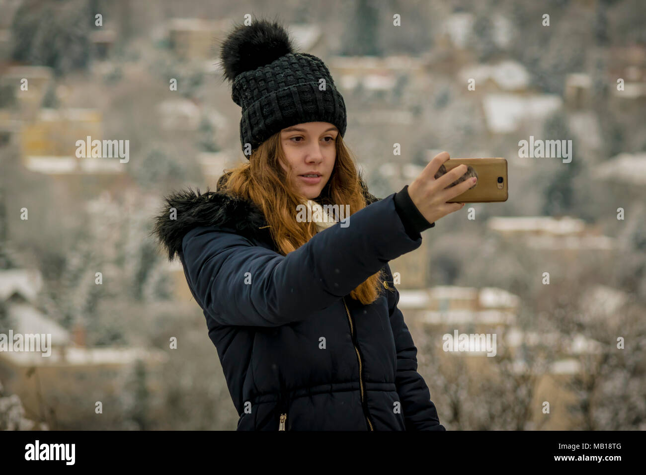 Pretty teen girl in snow, takes selfie with phone. Half body portrait of beautiful Caucasian teenage girl, blurred snowy city in background. - Stock Image