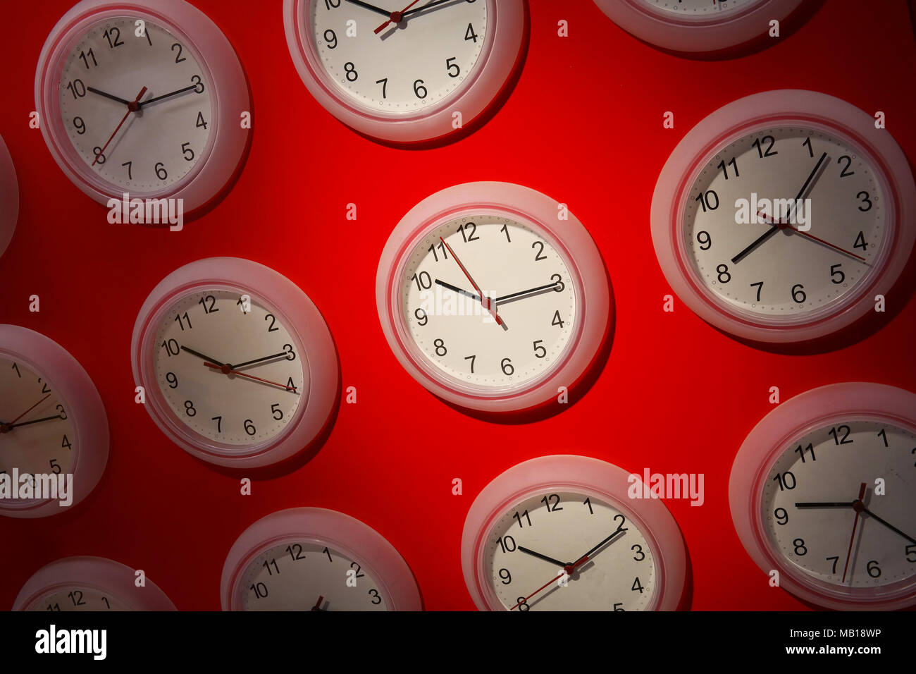 Clocks on a red background - Stock Image