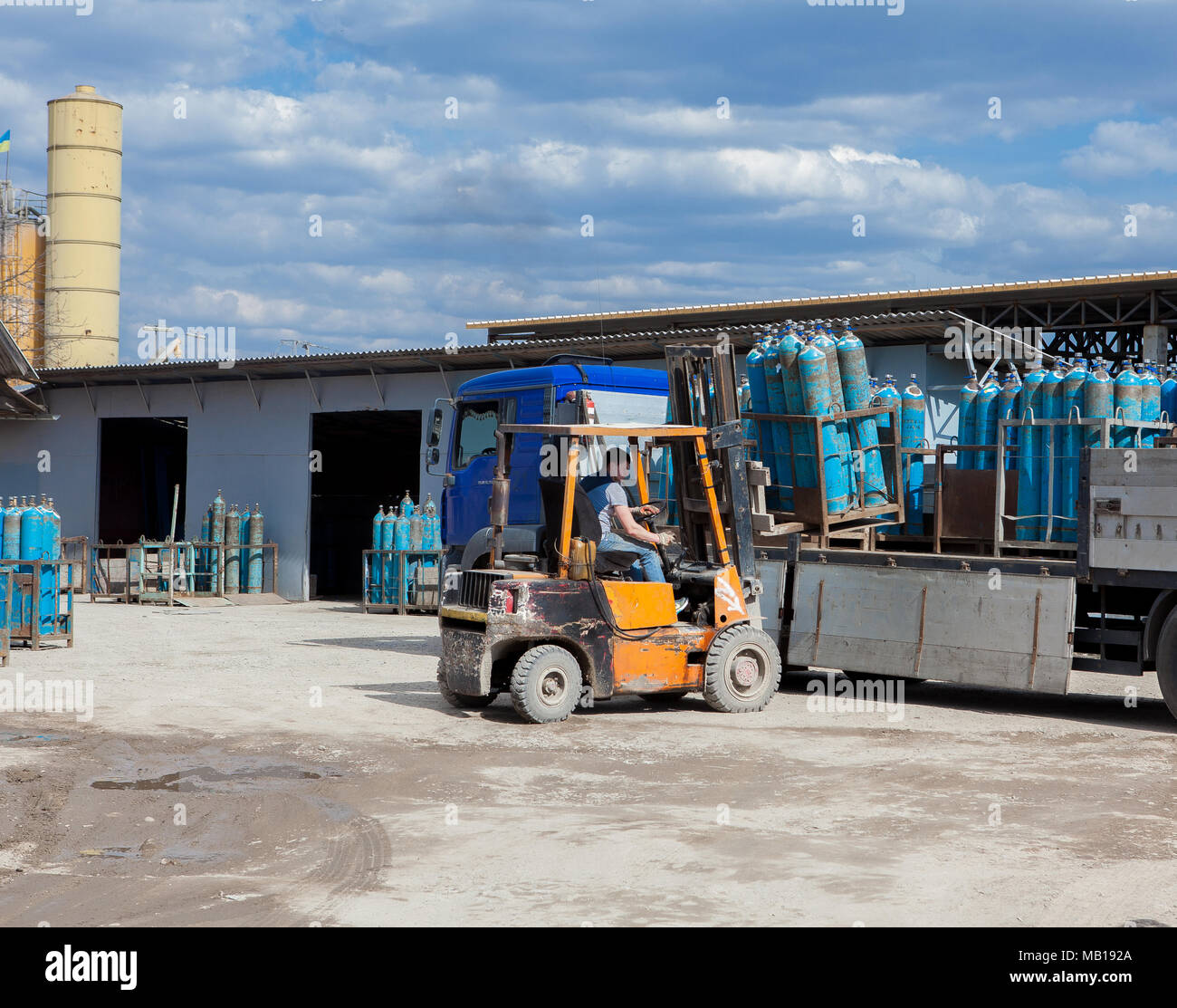 Truck for transportation of gas cylinders. The car delivers gas to shops, restaurants and city dwellers. ForkLift unloading of a truck with gas cylinders - Stock Image
