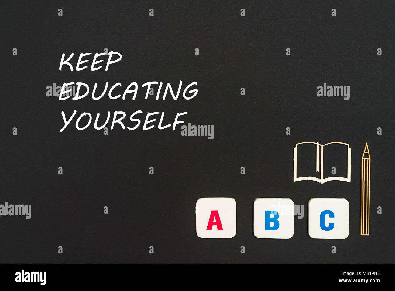 concept english school, text keep educating yourself, abc letters, chipboard miniature book, pen on blackboard - Stock Image