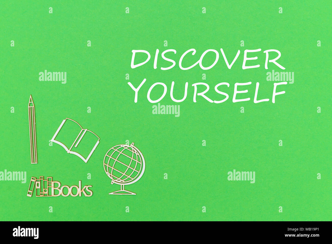 concept school for kids, text discover yourself, school supplies wooden miniatures on green backboard - Stock Image