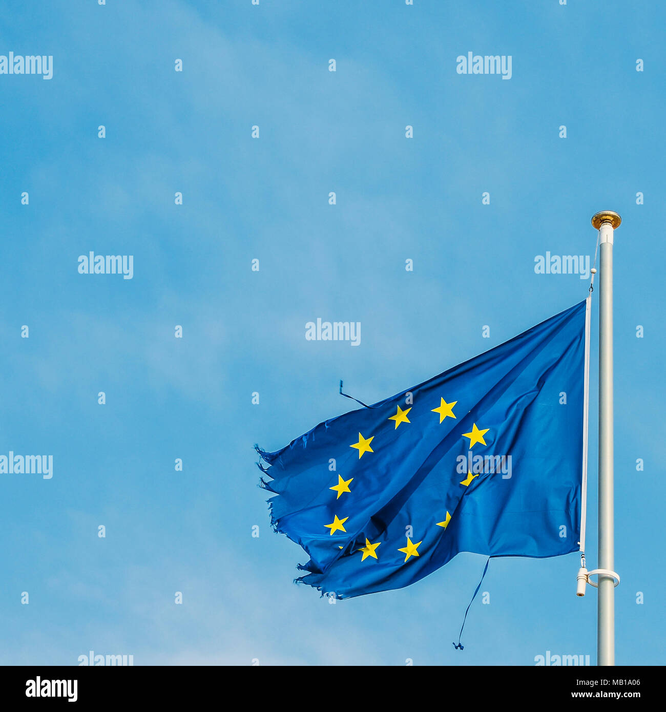 European Union flag on a mast proudly moving in the wind despite the ripped up pieces of cloth on the edges which is perhaps a metaphor for the serious crisis currently facing the economic block. - Stock Image