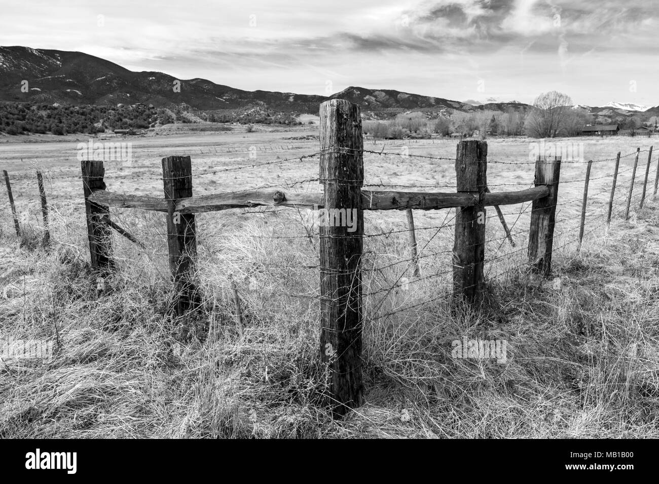 Infrared; black & white view of wooden fencepost and barbed wire; Vandaveer Ranch; Salida; Colorado; USA - Stock Image