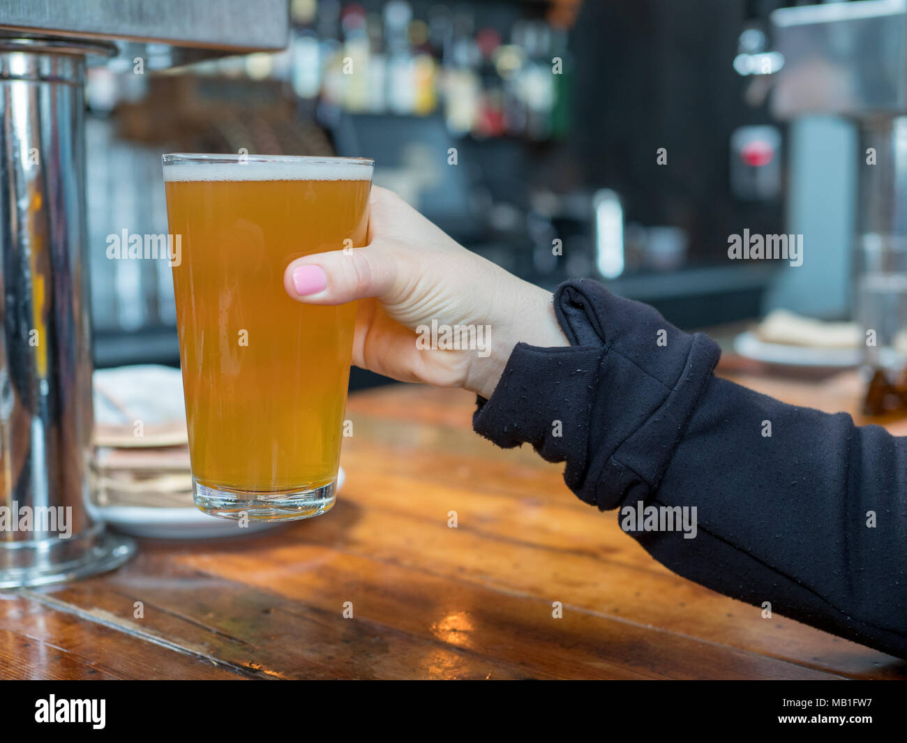 Woman lifting up pint glass of IPA beer in a bar in a brewery - Stock Image