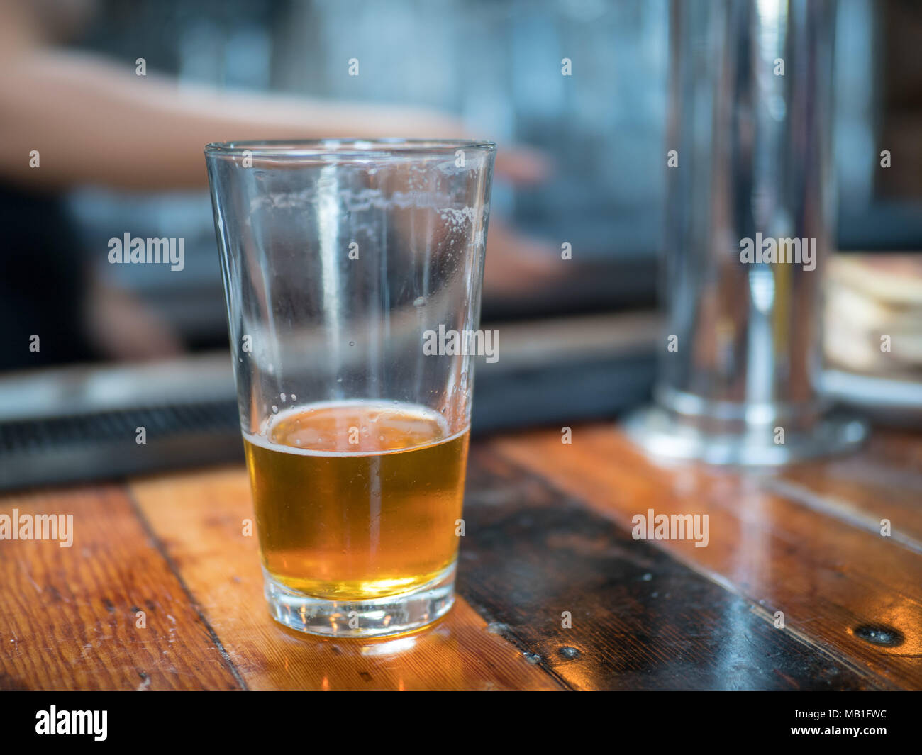 Almost empty pint glass of beer sitting on wooden bar for last call - Stock Image