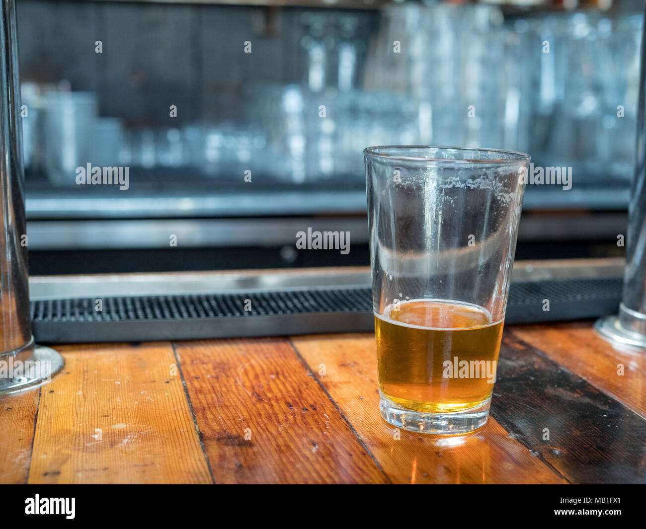 Almost empty pint glass of beer sitting on woodencountertop for last call. Bar in background - Stock Image