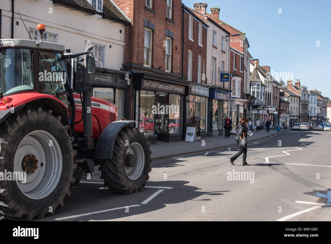 A women crosses the road in Newport, Shropshire whilst a farmers tractor  waits patiently for her to cross the road in the sunshine - Stock Image