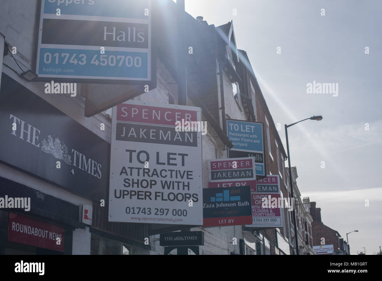 Many shop letting agent boards mounted to a wall in Shrewsbury as the town continues to struggle to fill vacant shops on the high street and the mall - Stock Image