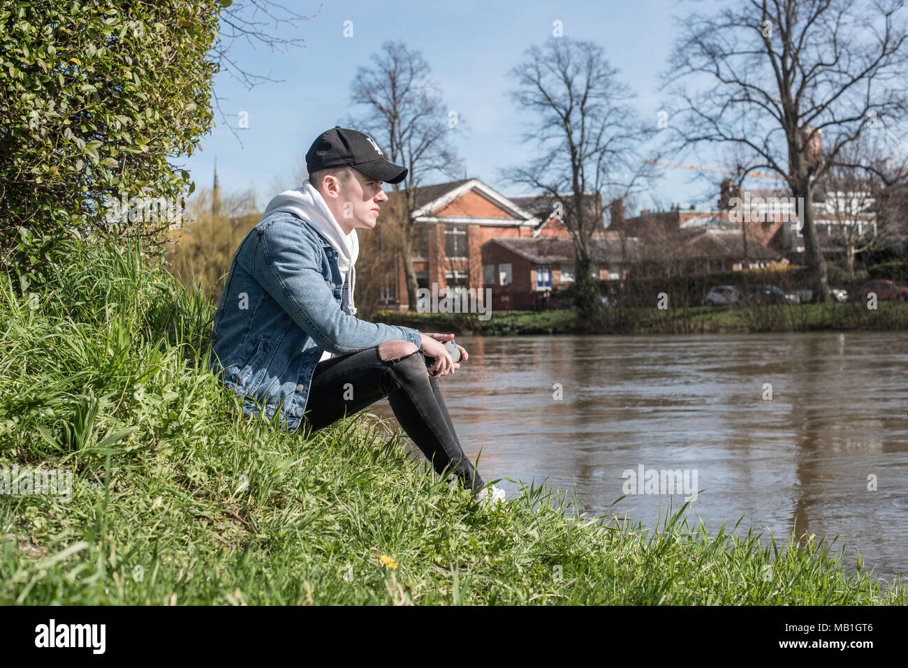 Young male youth sitting next to the river in the beautiful spring sunshine wearing denim jacket and black baseball hat - Stock Image