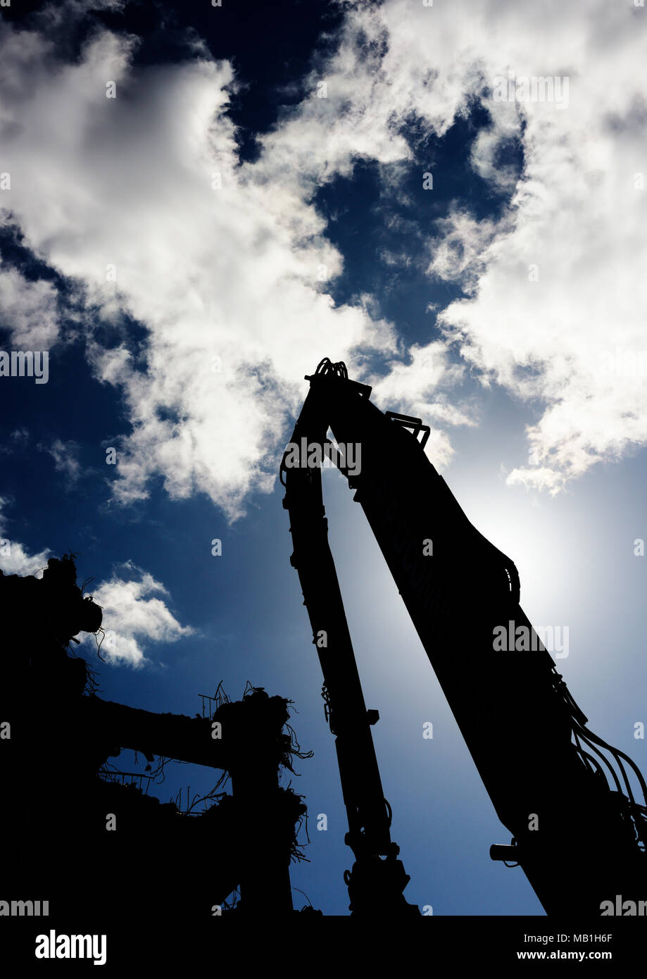 High reach excavator and partly demolished building in silhouette sun backllighting machine partly demolished building and clouds in bury  lancashire - Stock Image