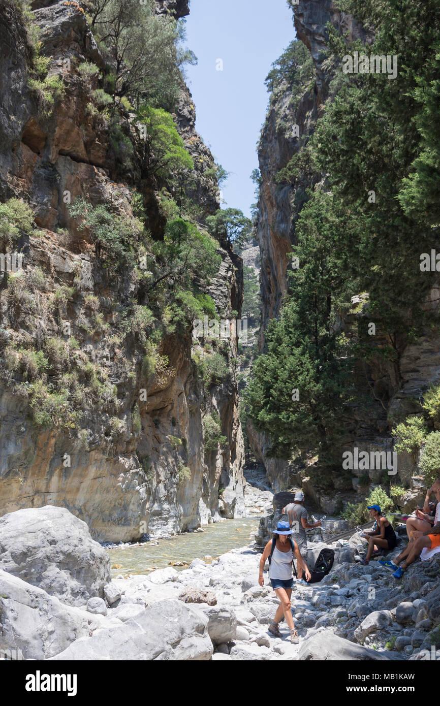 Walkers walking through narrow Portes section of the Samaria Gorge. Agia Roumeli, Sfakia, Chania Region, Crete (Kriti), Greece - Stock Image