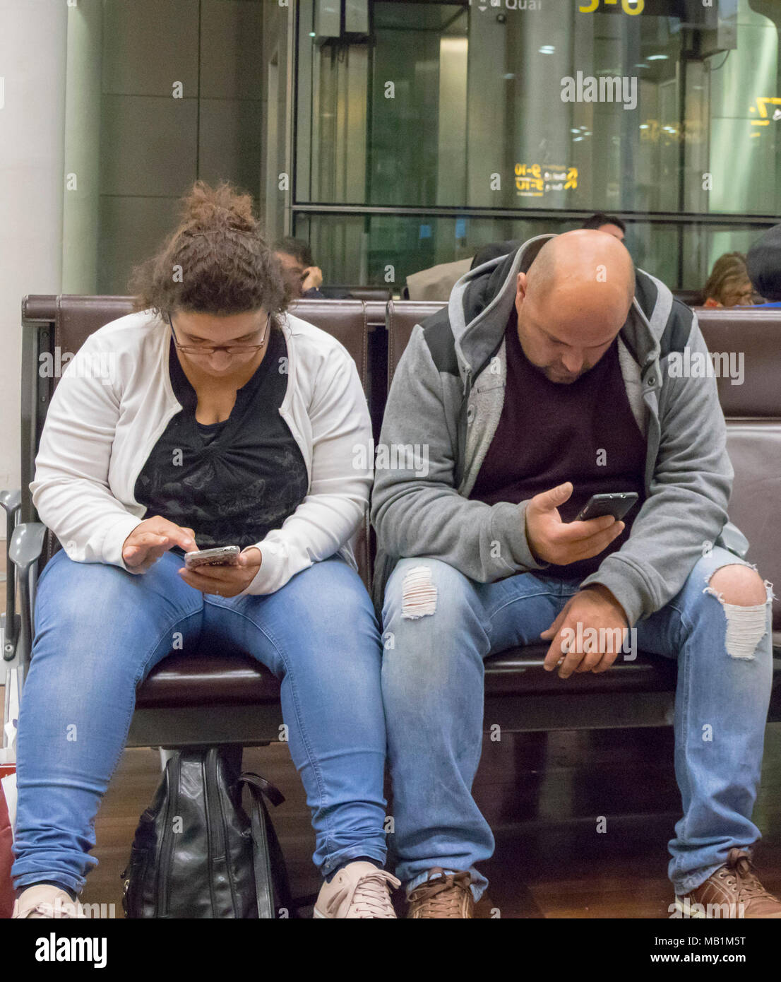 people in Eurostar waiting room of St Pancras station, London, England, all using mobile phones - Stock Image
