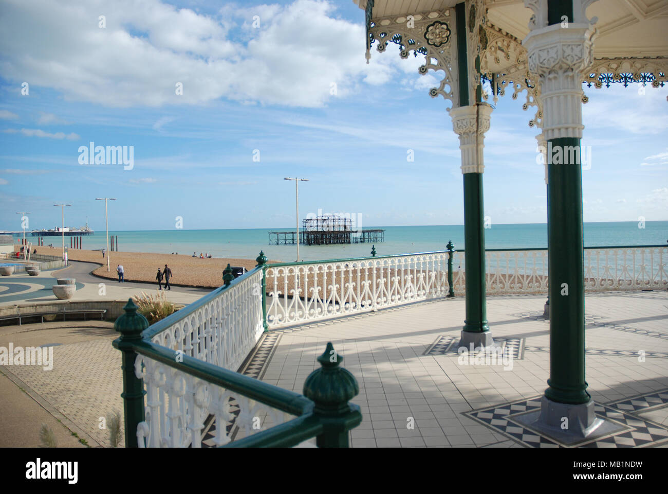 The side view of the Brighton Bandstand with the view of The West pier in the background as well as a partial far off view of Brighton Pier - Stock Image