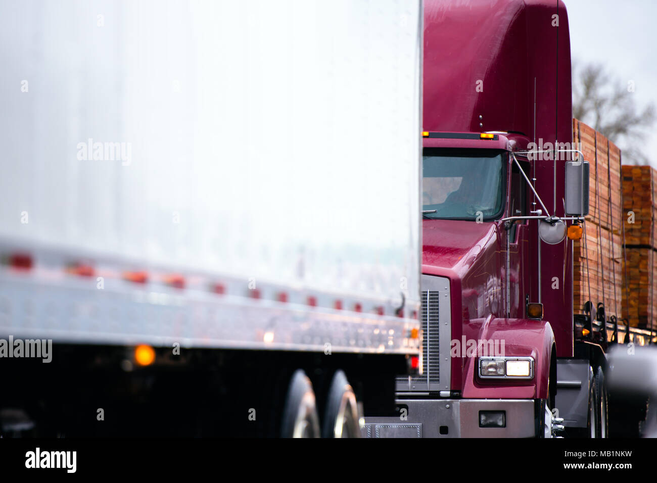 Big Rig Classic Powerful Dark Red Semi Truck Tractor Transporting Stacks Of Boards Lumber Wood On Flat Bed Semi Trailer Driving In Convoy Behind Anoth Stock Photo Alamy